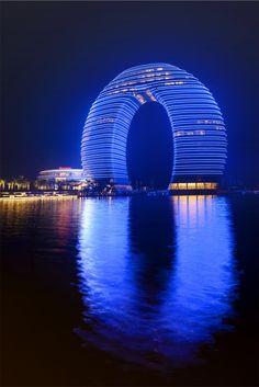 Formant une sorte d'anneau au-dessus du lac Tai en Chine, cet hôtel appartenant à la chaine hôtelière Sheraton Hotel est une formidable construction disposant de plus de 300 chambres qui offrent une vue imprenable sur la ville d'Huzhou et ses environs.  Pensé et réalisé par l'architecte Ma Yansong du studio d'architecture MAD Architects basé à Pékin en Chine