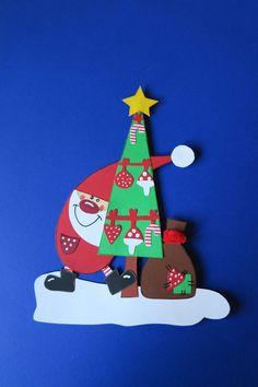 """Hier gibt es ein schönes Fensterbild für die Winter- und Weihnachtszeit: """"lustiger Weihnachtsmann"""" mit geschmücktem Baum und Sack Das Motiv ist beidseitig aus Tonkarton gebastelt und..."""