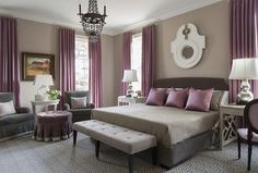 Purple and gray bedroom features walls painted warm gray lined with a dark gray bed dressed in gray bedding and purple pillows flanked by a white nightstand to the left and a gray desk and purple round back chair on the right unified by silver double gourd lamps.