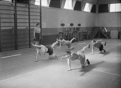 FACTORY WELFARE WORK: WELFARE AT PILKINGTON'S GLASS FACTORY, ST HELENS, LANCASHIRE, ENGLAND, UK, 1944  D 20087  Women do stretching exercises in the gymnasium at the factory rehabilitation centre, (probably at Pilkington's glass works at St Helens), as part of their recovery after an injury. They are kneeling on the floor, with one leg and the opposite arm...