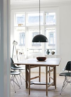 Wooden table, black Eames chairs & black Ikea lamp