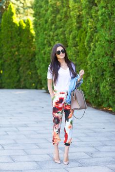 Rachel Parcell is wearing floral silk pant from Nordstrom, white T-shirt from Alexander Wang, bag from Valentino, shoes from Christian Loubo...