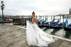 Flowy wedding dress in the wind as bride strolls by the Venetian waters // Designer Julie Vino's sexy wedding dresses which feature lavish laces, intricate sheer details and bodices encrusted with jewels, were inspired by the romantic city of Venice, Italy.
