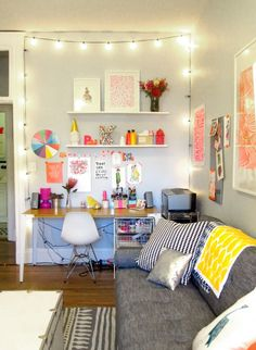 bright & happy workspace. love the strung lights and the artwork taped on the wall.