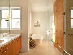 White walls and natural wood finishes inject a feeling of calm cleanliness into this contemporary master bath. The faucet for the freestanding tub is wall-mounted, and a hammered metal table keeps bathing implements in a handy, reachable spot. Multiple windows bring in loads of light.