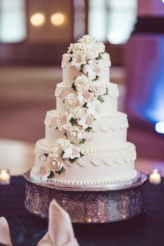 Four-tier white + pink wedding cake with cascading white sugar flowers on silver cake stand {Jessika Feltz Photography}