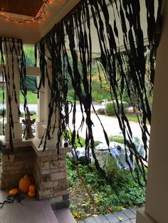 HOW TO:  black plastic cut in strips and pulled to create these awesome strands to hang all over the porch, doorways, over garage, etc.  Super cheap and super simple to make.  But dramatic look!  A must for your Halloween decor this year!