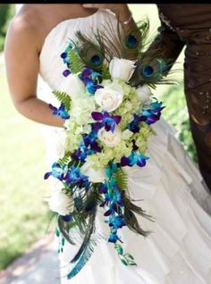 Beautiful blue orchid bouquet -(love this color scheme minus the peacock feathers & I wish it was round)