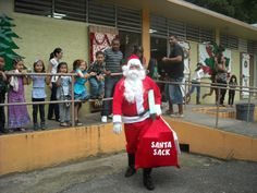 Person wearing Santa Claus bringing toys to school's children.