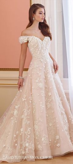 Off-the-shoulder tulle and sequin tulle over organza and taffeta full A-line gown features Chantilly lace with Venise lace appliqués, dipped neckline, bodice and skirt adorned with three-dimensional organza flowers, horsehair hemline, chapel length train.