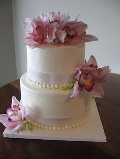 Two tiers of white cake; simple  ornamental lily flowers, and pearl-like granules around each cake in tiers look elegant and understated