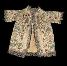 Miniature robe made from two coifs        English, late 16th–early 17th century         England  Dimensions      29 x 33 cm (11 7/16 x 13 in.)  Medium or Technique      Linen with silk and gold-colored metallic threads and spangles embroidery, gold-colored metallic bobbin lace, linen ties, and silk figured weave lining  Classification      Costumes     Accession Number      38.1386
