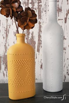 DIY wine bottle vases decorated with puff paint. Puff paint wine bottle vases Don't pitch your empty wine bottles; turn them into wine bottle vases! Puff paint and spray paint are all you need to make your design look fabulous!