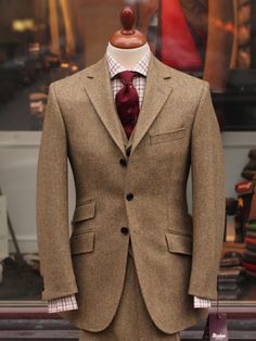 Light brown tweed suit, white shirt with red & light grey tattersall, red tie