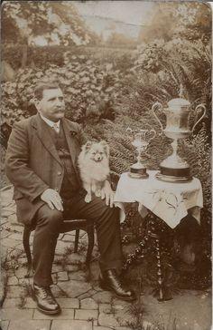 PRIZE WINNING POMERANIAN SPITZ WITH MAN & TROPHIES REAL PHOTO DOG POSTCARD