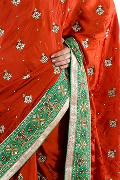 The pleats of the saree have embroidery and stone work. The saree has a green & golden border which is decorated with thread embroidery, stones and sequins.