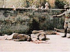 German soldier finishes off Serbian civilians executed at random in Pancevo, north of Belgrade, Serbia, on April 22, 1941. The executions were filmed in color by Gottfried Kessel of the propaganda company of the Gross Deutschland Regiment.