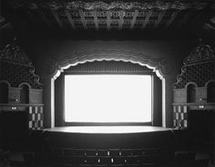 Black and White Pictures of Cinemas   Photographer Hiroshi Sugimoto began his Theaters series in 1978. Since he photographs cinemas and its screens. come to this result, he places his camera and catches a long exposure photograph during all the movie. He can capture all the room details and the screen turns into a rectangular luminous source.