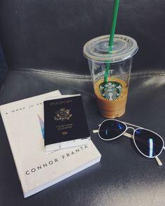 Airport essentials Starbucks sunglasses book passport