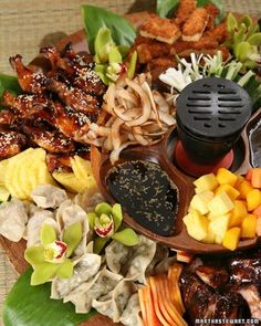 The centerpiece of any Polynesian party, this pupu platter is piled with baby pork ribs, shrimp toast, glazed chicken wings, pot stickers, and tropical fruit.