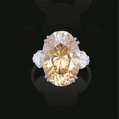 A FANCY DEEP BROWNISH YELLOW DIAMOND RING, BY WEBB  Set with an oval-cut fancy deep brownish yellow diamond weighing 19.09 carats to the pear-shaped diamond shoulders and plain platinum hoop Signed Webb