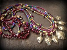 stunning assortment of Kuchi Brass charms nestled in between stones of Garnet and brass spacers. 4 strands of glass seed beads in the most amazing