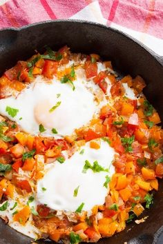 Shakshuka - poached eggs dish with spicy tomatoes, peppers and onions