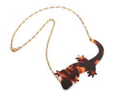 Diseño realizado en acetato con cadena baño en oro, se inspira en la Salamandra común, Salamandra salamandra.