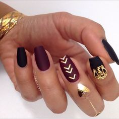 Matte maroon and black nails with gold accents.