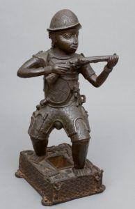 Os europeus eram frequentemente representados, na arte africana de Benin, com armadura e armas. Os arcabuzes e canhões dos europeus, contudo, não intimidaram os obás que conservaram seus domínios até o final do século XIX. Bronze, Edo/reino de Benin, Nigéria, Museu Britânico.
