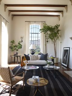 Cream plastered walls and cotton/linen draperies. Dark wood beams held up with stone corbels. Large, navy striped cotton rug. Woven armchair, wooden daybed with white and navy striped pillows. Large potted plants, metal tray tables, shiny silver oversized
