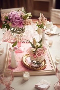 More gorgeousness...fabric-stuffed frames, arrangements elevated on pink depression glass cake stands...sigh.