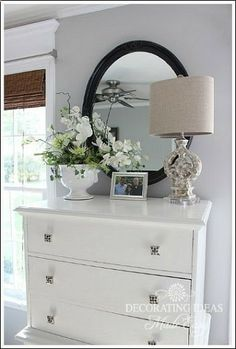 The black oval mirror really grounds this look where you have a white or light-colored chest of drawers and other objects. ~ irj