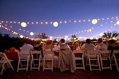 Love the play with the paper lanterns, stringed lights, and fabric garland for lighting outdoors.