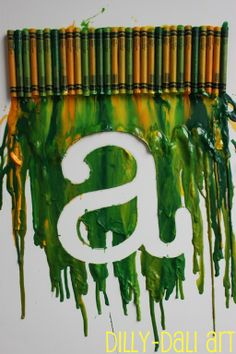 Dilly-Dali Art: Melted Crayon Art.  This is my other idea for something to hang over her crib.  I'm not very crafty, though, so I have a feeling the letter bit could turn out shaky for me.  Either way, I think crayon art is happening in her room!