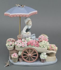 "Lot 7, A large Lladro group of a girl flower seller before a barrel of flowers beneath a parasol 11"", est £150-200"
