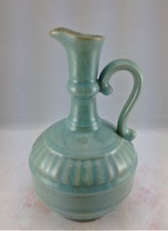 A VERY RARE GUAN STYLE EWER WITH BLUISH GREEN GLAZE.  Note: A heavily potted globular body with molded impressed decoration, the top of the neck opening to a wide 'U' shaped spout and scrolled handle in the shoulder, covered overall with bluish green glazed with crackles. The distinctive shape of this ewer is derived from 15th century Imperial prototype decorated in underglaze-blue. Yongzheng seal mark and of the period. Height: 26,5 cm.