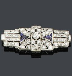 An art deco sapphire and diamond brooch, circa 1925 The mount with pierced detail set throughout with single-cut diamonds, the central collet mounted old brilliant-cut diamond flanked by tapered sections of calibré-cut sapphires, length 3.9cm.