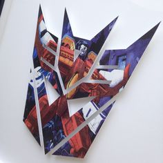 "****handmade transformers LOGO****  details-- icon is hand-cut using recycled comic book pages.  mounted on foam board, 'float' mounted on board, and framed. Icon will measure 6"" tall and consists of eight intricate separately hand-cut pieces.  no two are alike! a great addition to a nursery or kid's room! (icon shown is a sample of what can be made for you!)  framing-- icon will be framed in a 8"" x 10"" black <or> white frame with glass front. carefully packaged for shipping.  once payment…"