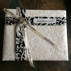 """A graduation gift wrapped in ecru Anaglypta wallpaper.  Black/white folded wrapping paper was used for ribbon.  """"Good Luck"""" stamped on plain cream satin ribbon and an old brooch to add a little bling for the graduate."""