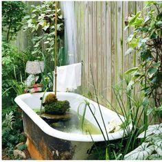 oude badkuip als regenton in tuin