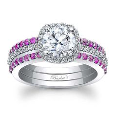 Stunning, in vogue, this white gold diamond halo engagement set will capture the eye of many admirers. Micro pave diamonds encircle the low profile round diamond center and cascade down the dainty shank. Two shared prong set pink sapphire wedding bands grace the sides for a look of sheer elegance.<br />  <br />  Also available in 18k and Platinum.