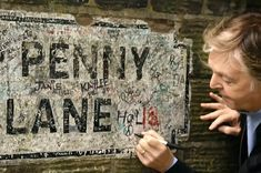 Penny Lane — immortalized in the song of the same name — is indeed a real street in Liverpool. In fact, during Carpool Karaoke, Paul stopped to autograph this street sign, and it's still there! Paul Mccartney, Beatles Love, John Lennon, John One, Sir Paul, The Late Late Show, Love Me Do, Penny Lane, The Beatles