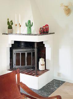 Swedish Corner Fireplace with Cactus Vase, Matryoshka Nesting Dolls on Mantle | Design*Sponge