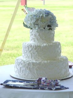 "this cake's intricately designed icing and assortment of flowers on top are both the ""icing on this cake"" #wedding #cake"