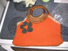 I love the design of this recycled sweater purse, but wish it had a different handle. Rattan says 'summer' to me, not 'sweater'.