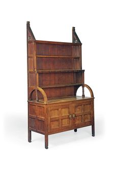 EDWARD WILLIAM GODWIN (1833-1886) BOOKCASE, DESIGNED FOR DROMORE CASTLE, IRELAND, CIRCA 1870 probably manufactured by Reuben Burkitt, wainscot oak with brass pulls and fittings 88 in. (223.5 cm.) high; 48¾ in. (123.8 cm.) wide; 21½ in. (54.7 cm.) deep
