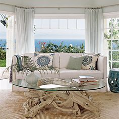 Sea-foam walls, Turkish throw pillows beach ocean view white couch living room with driftwood table.