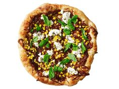 Onion-Ricotta Pizza (No. 31) : Stretch dough into two thin 9-inch rounds. Spread each with caramelized onions. Top with thyme, corn, olive oil, salt and pepper. Mix 2 tablespoons chopped oregano with 1/3 cup ricotta. Dollop over corn before baking. Bake until golden; garnish with basil.
