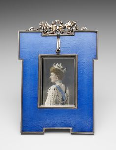 This blue lacquer and silver frame is unusual, lacquer being a relatively rare technique in Fabergé's oeuvre. It was produced in the workshop of Anders Nevalainen, who specialised in frames and enamelled objects. The coloured photograph of Queen Alexandra by W&D Downey dates from 1913.